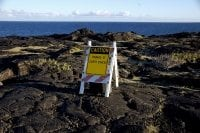 Photo of caution sign on lava flow